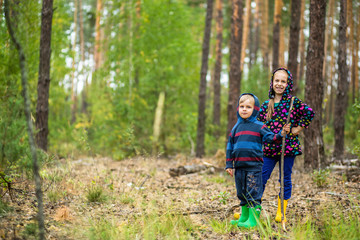 Children walk in the forest with canes.