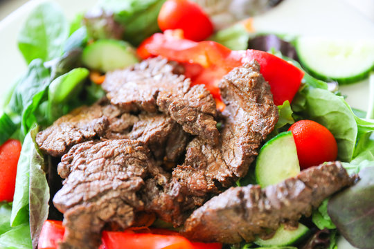 Delicious juicy barbequed steak, grilled meat  beef ( lamb ) garnished with tomatoes ,tomatoes and vegetables