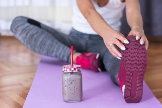 Attractive girl stretching legs and with detox smoothie in jar on purple yoga or fitness mat at home. Sport and recreation concept. Close up, selective focus