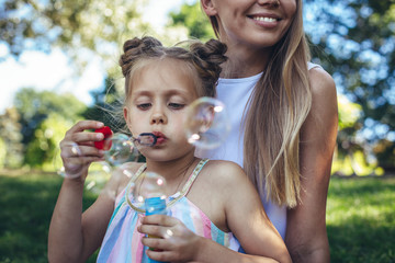 Waist up portrait of playful kid blowing soap bubbles in park. Her mother is sitting on grass behind her and smiling