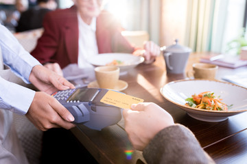 Hand of customer paying with contactless credit card with NFC technology at the restaurant