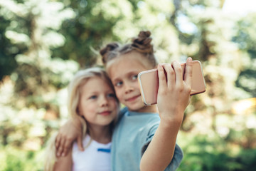 Focus on kid hand holding smartphone outside and making selfie. Little girls are happy and delighted amusing themselves on nature