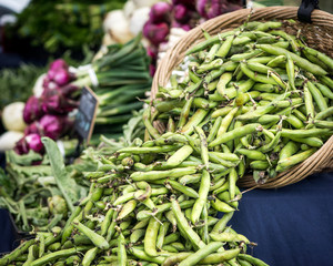 Large basket of fava beans at a farmers's market vegetable stand.
