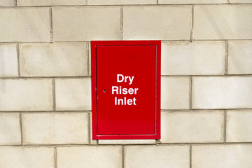 Dry riser inlet box red on brick wall for emergency fire services water connection for hose brigade engine at shopping mall retail park