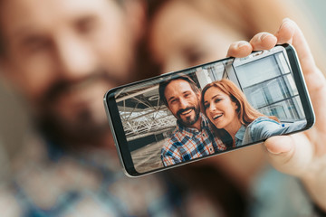 Close up display of contemporary phone. Portrait of outgoing bearded male and smiling lady taking picture on gadget