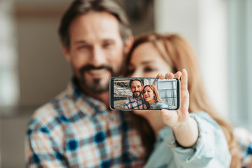 Close up screen of modern phone with photo of cheerful man and outgoing woman. She holding appliance in arm