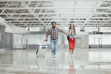 Wall Mural - Full length portrait of worried male and woman running with baggage indoor. They late for flight