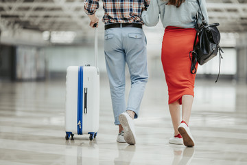 Close up woman and man legs walking at airport. Female holding guy hand. He keeping modern suitcase. Journey concept