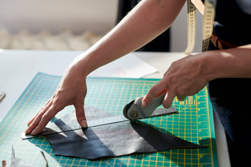 Close-up of female tanner cutting a piece of black leather along the line for making bags at her workplace