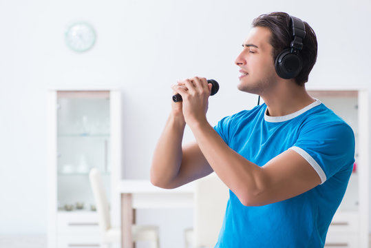 Young handsome man singing karaoke at home
