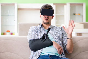 Young student man with hand injury wearing virtal glasses