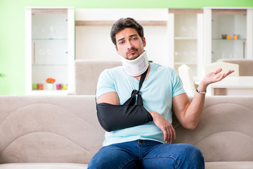 Young student man with neck and hand injury sitting on the sofa