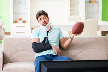Man with neck and arm injury watching american football on tv