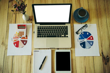 Sideview of office desktop with blank laptop and various office tools