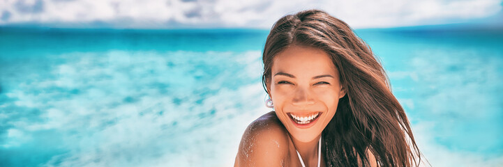 Beautiful Asian woman smiling relaxing on summer beach sunbathing banner panorama.
