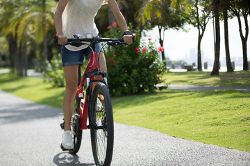 Woman riding mountain bike in tropical park