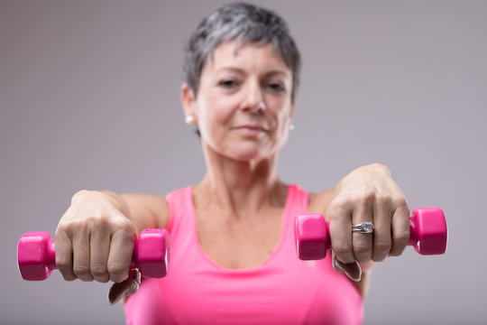 Older woman working out with a pair of dumbbells