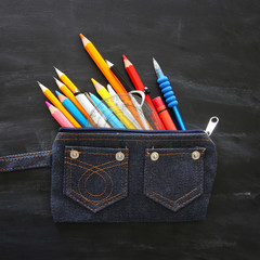 Top view of pencil case with stationery over chalkboard background.