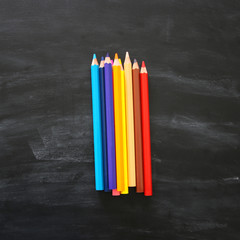 Top view of colorful pencils over chalkboard background.