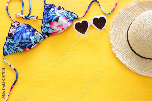 26d8b858f2 Top view of fashion female swimsuit bikini and white fedora hat over yellow wooden  background. Summer beach vacation concept.