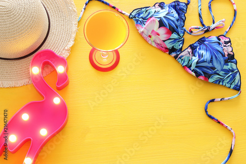 a326749df5 Top view of fashion female swimsuit bikini and hat over yellow wooden  background. Summer beach vacation concept.
