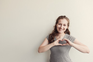 Happy young woman making her hands in heart shape