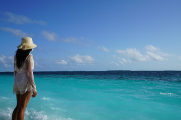 Young woman standing along the beach in the Maldives