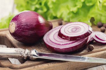 Red onion sliced ​​with rings on old kitchen board, knife, salad, pea pepper.