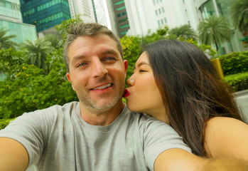 young happy and attractive mixed Asian Caucasian ethnicity couple in love taking selfie picture together smiling and kissing enjoying honeymoon trip
