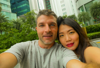 young happy and attractive mixed Asian Caucasian ethnicity couple in love taking selfie picture together smiling cheerful enjoying holidays travel