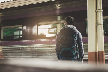 Rear view of asian young hipster man standing and waiting train on platform.
