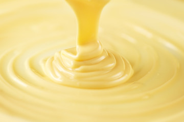 White chocolate. Pouring melted liquid white chocolate. Closeup of molten liquid hot chocolate swirl. Confectionery