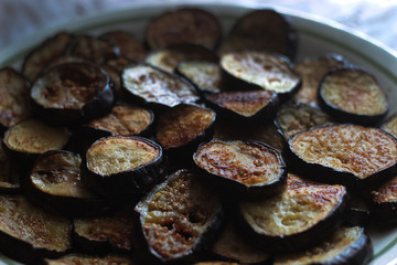 slices of fried eggplant close-up in a large round plate