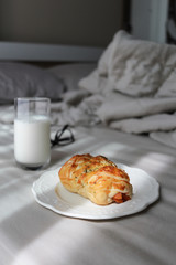 Plate of sausage roll with milk are on top of the bed. Breakfast in bed concept.