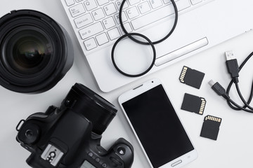 top view of camera, lenses, photography equipment, smart phone and computer over white
