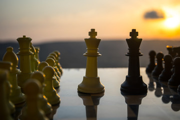 chess board game concept of business ideas and competition and strategy ideas. Chess figures on a chessboard outdoor sunset background.