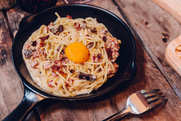 Fettuccine Carbonara yolk bacon served in black pan on wooden table.
