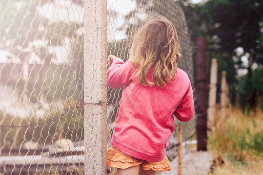 A little girl standing near the fence with barbed wire. The concept of emigrants, lost childhood.