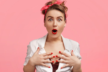 Emotive gorgeous lady keeps hands on breast, stares with bugged eyes and bated breath, can`t believe in something amazing, wears red headband, has red painted lips and manicure, isolated on pink