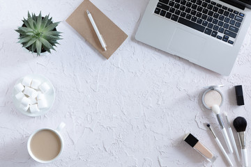 Modern and fashion office desk with laptop, blue notebook, mobile phone, pen, marshmallows and coffee cup, flat lay. Top view of female table with copy space