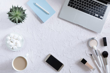 Top view of woman beauty blogger working desk with laptop, notebook, decorative cosmetic, flowers and coffee cup, envelope on white pastel table. Flat lay background.