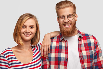 Happy young family couple with cheerful expressions, dressed casually, have white teeth, stand closely to each other. Optimistic hipster has ginger beard wears checkered shirt has date with girlfriend