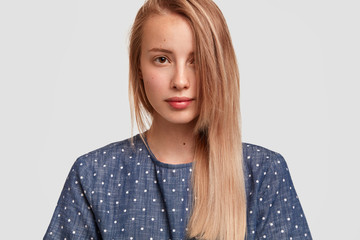 Wall Mural - Cute young female with long hair combed on one side, looks seriously, shows her healthy perfect skin, dressed in polka dot blouse, poses against white background. People, beauty, lifestyle concept