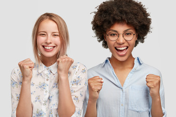People, diversity and celebration concept. Joyful mixed race women clench fists with triumph, celebrate successful day, wears fashionable shirts, pose in studio. Yeah, we did it! Multiracial friends