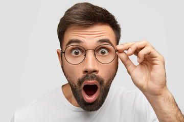 Close up portrait of stunned bearded young guy drops jaw, has bugged dark eyes, sees something unbelievable and surprising, has eyewear, isolated on white background. People, emotions concept