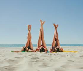 Woman in bikini sunbathing on beach with legs raised to the sky