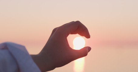 young female hand catches sun in her hand