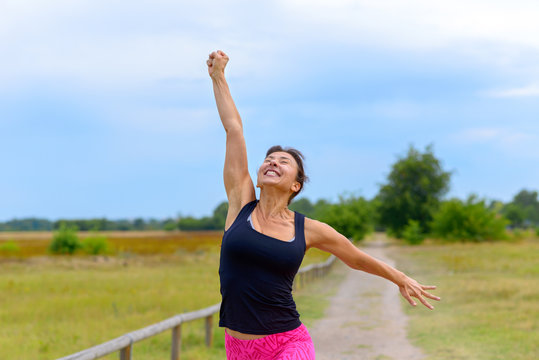 Happy woman cheering and celebrating after working out jogging