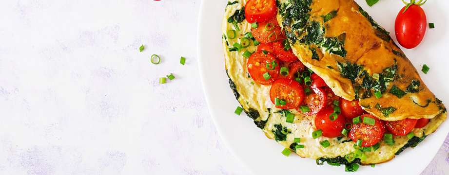 Omelette with tomatoes, spinach and green onion on white plate.  Frittata - italian omelet. Top view. Flat lay. Banner