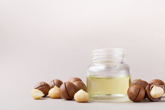 Cosmetic macadamia oil and heap of nuts on table.
